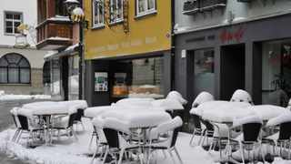 Snow-covered tables and chairs are seen outside a restaurant in St Gallen, eastern Switzerland, on Sunday after a weekend of winter weather.