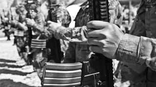 Soldiers stand in formation while holding an assault rifle.