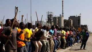 Striking mine workers armed with machetes, sticks, and spears march to a smelter plant at the Lonmin Platinum Mine near Rustenburg, Wednesday, Sep 12.