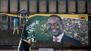Supporters of the opposition Movement for Democratic Change party (MDC) of Nelson Chamisa remove an election banner with the face of Zimbabwe's President Emmerson Mnangagwa in Harare, Zimbabwe. Picture: Siphiwe Sibeko/Reuters