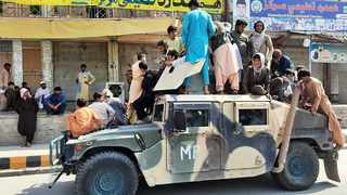 Taliban fighters and local residents sit on an Afghan National Army (ANA) Humvee vehicle along the roadside in Laghman province on August 15, 2021. Picture: AFP