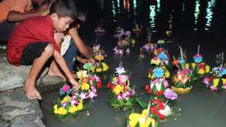 Thai children send their 'krathong', a small lotus-shaped float made of banana leaves, on a canal in the Thai capital during the yearly Loi Krathong festival.