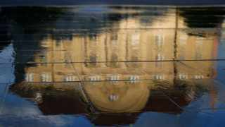 The Swiss central bank is reflected in a fountain in Bern, Switzerland.