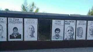 The faces of the 'Upington 26' trialists are seen on the monument, where one of the faces was blocked out and painted with black paint on Monday. Picture: Supplied
