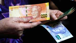 The rand broke below the key psychological mark of R14 to the dollar yesterday to touch R13.96, buoyed by positive sentiment as manufacturing output rose more than expected. Photo: AP Photo/Denis Farrell