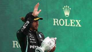 Third placed Mercedes' British driver Lewis Hamilton celebrates on the podium after the Formula One Hungarian Grand Prix. Photo: AFP