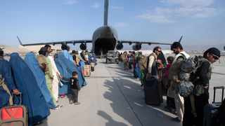 """This handout photo courtesy ot the US Air Force shows US Air Force loadmasters and pilots assigned to the 816th Expeditionary Airlift Squadron, load passengers aboard a US Air Force C-17 Globemaster III in support of the Afghanistan evacuation at Hamid Karzai International Airport (HKIA), Afghanistan,, August 24, 2021. - Afghans on August 25, hurried to escape Taliban rule, but Western officials said the group had made assurances that some evacuations would be permitted after next week's US withdrawal deadline. Over 80,000 people have been evacuated since August 14, but huge crowds remain outside Kabul airport hoping to flee the threat of reprisals and repression in Taliban-led Afghanistan. (Photo by Donald R. ALLEN / US AIR FORCE / AFP) / RESTRICTED TO EDITORIAL USE - MANDATORY CREDIT """"AFP PHOTO / US AIR FORCE / Master Sgt. Donald R. ALLEN """" - NO MARKETING - NO ADVERTISING CAMPAIGNS - DISTRIBUTED AS A SERVICE TO CLIENTS"""
