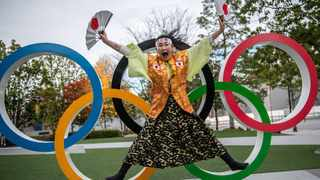 This picture taken on December 19, 2020 shows Olympic super-fan Kyoko Ishikawa posing in front of an Olympic rings installation outside the National Stadium in Tokyo. Picture: Philip Fong/AFP
