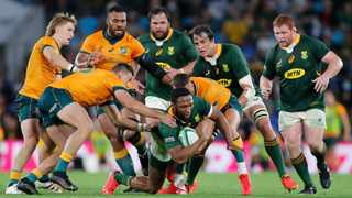 Tom Banks (L) and Quade Cooper (R) of Australia tackle Lukhanyo Am (C) of the Springboks during the Rugby Championship Round 3. Photo: Regi Varghese/AFP