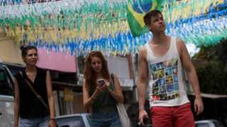 Tourists walk on a street decorated for the upcoming World Cup, in Rio de Janeiro, Brazil.