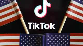 U.S. flags are seen near a TikTok logo in this illustration picture taken July 16, 2020. REUTERS/Florence Lo/Illustration