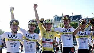 UAE Team Emirates rider Tadej Pogacar of Slovenia wearing the yellow jersey celebrates with his teammates after winning the Tour de France. Photo: Philippe Lopez/Reuters