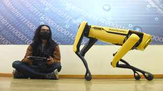 UJ Masters student in AI and Robotics Devakshan Naicker with a mobile four-legged, animal-mimicking robot with artificial intelligence (AI). The University bought the from Boston dynamics in the United States. The robot which the university hasn't named yet can walk, climb stairs, run and even hop. Picture: Itumeleng English/African News Agency(ANA)