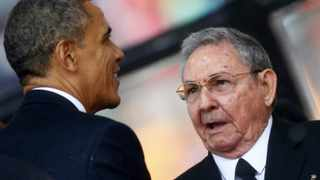 US President Barack Obama (L) greets Cuban President Raul Castro before giving his speech at the memorial service for late South African President Nelson Mandela at the First National Bank soccer stadium in Johannesburg. REUTERS/Kai Pfaffenbach