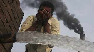 Unhealthy: A labourer drinks water as smoke rises from a chimney of a brick factory at Togga village on the outskirts of Chandigarh, India. A new study looks at the health effect of toxic industries on people.   Picture: Reuters