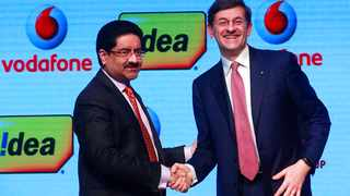 Vodafone Group CEO, Vittorio Colao, right, shakes hand with Aditya Birla Group chairman, Kumar Mangalam Birla after a press conference in Mumbai, India, Monday, March 20, 2017. British telecom company Vodafone's Indian unit has announced a merger with Idea Cellular, a local company, creating the country's largest telecom operator with nearly 400 million customers. The companies said Monday that Vodafone will own 45.1 percent of the combined company and Idea, which is owned by India's Aditya Birla Group will have a 26 percent stake, while the rest will be owned by public shareholders after the merger, which is expected to be completed next year. (AP Photo/Rafiq Maqbool)