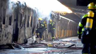WRECKAGE: Firefighters battle to extinguish a fire on one of two trains that were allegedly set alight at the Cape Town Central train station at the weekend. Picture: Ayanda Ndamane/African News Agency (ANA)