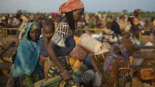 Women carry their belongings as they disembark from trucks carrying internally displaced people on the outskirts of the Central African Republic-Chad border town of Sido. File photo: Reuters