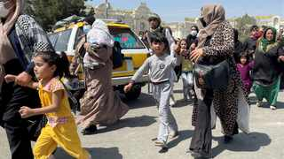 Women with their children try to get inside Hamid Karzai International Airport in Kabul, Afghanistan. Picture: Reuters