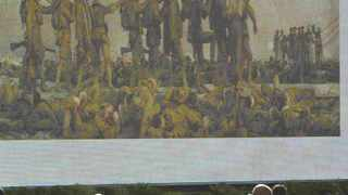 Workers pass an electronic billboard showing the 1919 painting Gassed by John Singer Sargent, which hangs in the Imperial War Museum.