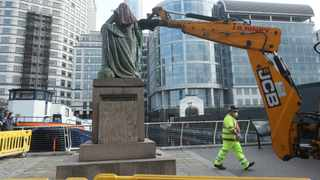 Workers prepare to take down a statue of slave owner Robert Milligan at West India Quay, east London, Tuesday, June 9, 2020, after a protest saw anti-racism campaigners tear down a statue of a slave trader in Bristol. London's mayor says statues of imperialist figures could be removed from the city's streets, in the latest sign of change sparked by the death of George Floyd. London Mayor Sadiq Khan says he is setting up a commission to ensure monuments reflect the city's diversity. (Yui Mok/PA via AP)