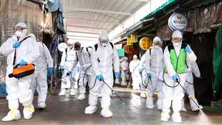 Workers wearing protective suits spray disinfectant as a precaution against the coronavirus at a market in Bupyeong, South Korea. Lee Jong-chul/Newsis via AP