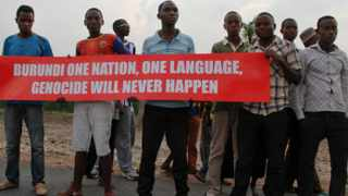 Young men hold a banner on the road that the convoy of the United Nations Security Council delegation took, in Bujumbura, Burundi. Picture: AP Photo