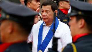 Philippine President Rodrigo Duterte salutes customs police as he arrives to witness the destruction of a fleet of 20 used luxury cars and SUVs as part of the 116th-anniversary celebration of the Bureau of Customs in Manila. Picture: Bullit Marquez/AP