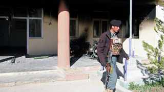 An Afghan policeman walks outside the government district building after a Taliban attack in Khawaja Omari district of Ghazni province. Picture: Reuters
