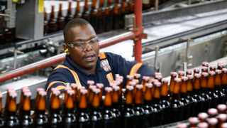 An employee inspects bottles of beer on a conveyor belt at the production line inside the East African Breweries Limited factory in Ruaraka factory in Nairobi