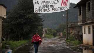 A woman walks under a banner in Uruapan, Mexico. File picture: Alan Ortega/Reuters