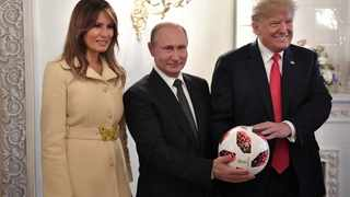 Russia's President Vladimir Putin (C), US President Donald Trump (R) and First Lady Melania Trump pose for a picture with a football during a meeting in Helsinki, Finland. Picture: Sputnik/Alexei Nikolsky/Kremlin via Reuters