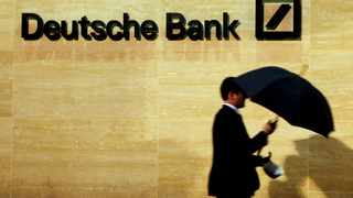 FILE PHOTO: A man walks past Deutsche Bank offices in London