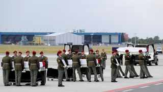 Members of an honor guard carry coffins of three Czech soldiers, who were killed by a suicide bomber in eastern Afghanistan, at the Vaclav Havel Airport in Prague