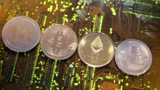 Representations of the Ripple, Bitcoin, Etherum and Litecoin virtual currencies are seen on a motherboard in this illustration picture. Photo; Reuters.