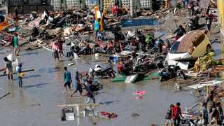 People survey outside the shopping mall which was damaged following earthquakes and a tsunami in Palu, Central Sulawesi, Indonesia, Sunday, Sept. 30, 2018. Rescuers try to reach trapped victims in collapsed buildings after hundreds of people are confirmed dead in a tsunami that hit two central Indonesian cities, sweeping away buildings with massive waves. (AP Photo/Tatan Syuflana)