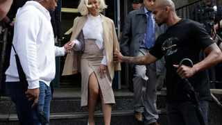 Rapper Cardi B is assisted by security guards as she leaves a police precinct, Monday, Oct. 1, 2018, in the Queens borough of New York. The rapper met with police as part of an investigation of her possible involvement in a fight at a strip club. (AP Photo/Mark Lennihan)