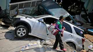 A woman walks past the wreckage of cars which was flattened by earthquake in Balaroa neighbourhood in Palu, Central Sulawesi, Indonesia. Picture: AP Photo/Dita Alangkara