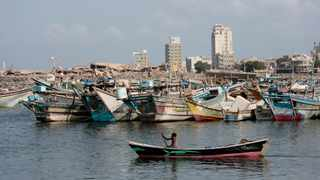 A fisherman paddles his boat past destroyed buildings on the coast of the port city of Hodeida, Yemen.  Picture: Hani Mohammed/AP