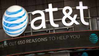 The AT&T logo is positioned above one of its retail stores in New York.  (AP Photo/Mark Lennihan, File)