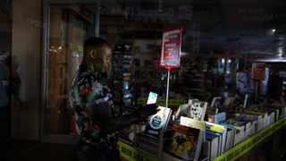 A staff member packs away books by the light of a mobile phone during an electricity load-shedding blackout in a shopping centre in Cape Town. Photo: African News Agency (ANA)