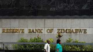 FILE PHOTO: People walk past the Reserve Bank of Zimbabwe building in Harare