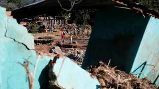 Survivors of cyclone Idai are seen through a destroyed bulding as they gather to receive aid at Coppa business center in Chipinge. Picture: Reuters/Philimon Bulawayo