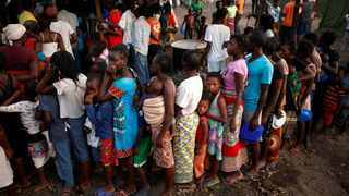 People queue for food in a camp for those displaced in the aftermath of Cyclone Idai in Beira, Mozambique. File picture: REUTERS/Mike Hutchings