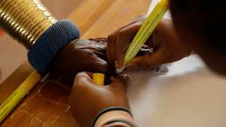 Esther Mahlangu, a contemporary South African artist, has her thumb ink-marked before casting her vote at KwaMhlanga, Mpumalanga. (AP Photo/Themba Hadebe)