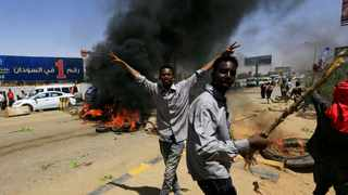 Sudanese protesters cheer as they burn tyres and barricade the road leading to al-Mek Nimir Bridge crossing over Blue Nile; that links Khartoum North and Khartoum. Picture: Mohamed Nureldin Abdallah/Reuters