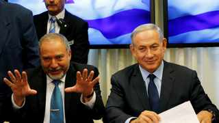 Avigdor Lieberman, head of far-right Yisrael Beitenu party, gestures as he sits next to Israeli Prime Minister Benjamin Netanyahu in Jerusalem as they sign a coalition deal to broaden the government's parliamentary majority. File picture: Ammar Awad/Reuters