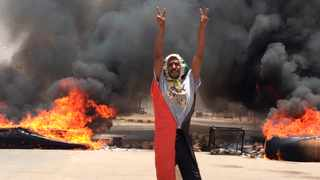 A protester flashes the victory sign in front of burning tires and debris on road 60, near Khartoum's army headquarters. Picture: AP