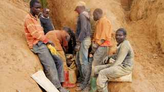 Artisanal gold miners sit outside a tunnel at an illegal mine-pit in Walungu