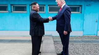 """In this Sunday, June 30, 2019, photo provided by the North Korean government, North Korean leader Kim Jong Un, left, and U.S. President Donald Trump shake hands over the military demarcation line at the border village of Panmunjom in Demilitarized Zone. The content of this image is as provided and cannot be independently verified. Korean language watermark on image as provided by source reads: """"KCNA"""" which is the abbreviation for Korean Central News Agency. (Korean Central News Agency/Korea News Service via AP)"""